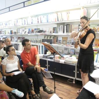 Cagliari, Libreria Murru, 24 luglio, ore 19:00, Scriviamo…nonostante tutto – Reading degli allievi del IV Corso di Scittura CreAttiva – ScriviAmo, Giulia Dessy in uno degli intermezzi musicali seguita attentamente dal pubblico